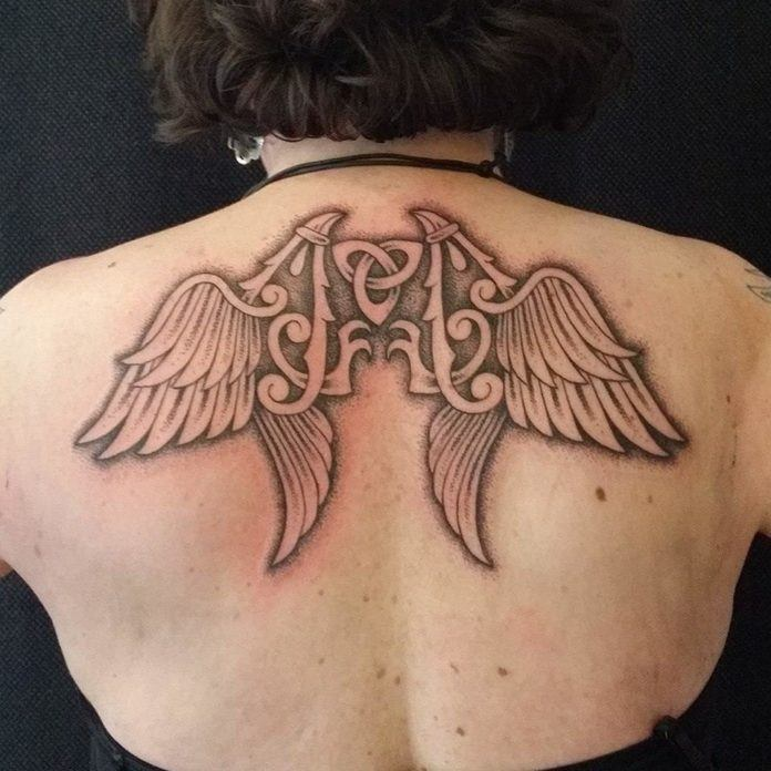 A celtic knot is at the heart of this wings tattoo across the shoulders - by Art on the Body tattoo studio
