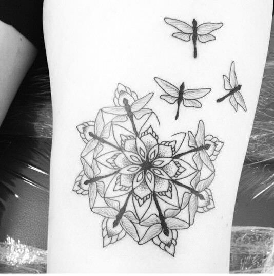 Dragonflies form a mandala shape around a flower in this spiritual nature tattoo