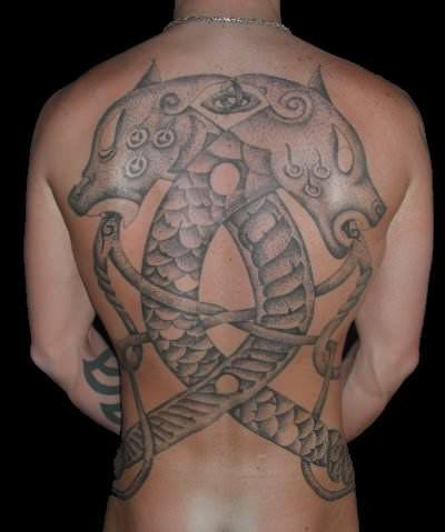 This full back tattoo by Art on the Body tattoo studio celebrates a scandinavian viking heritage by showing two dragons and celtic knots