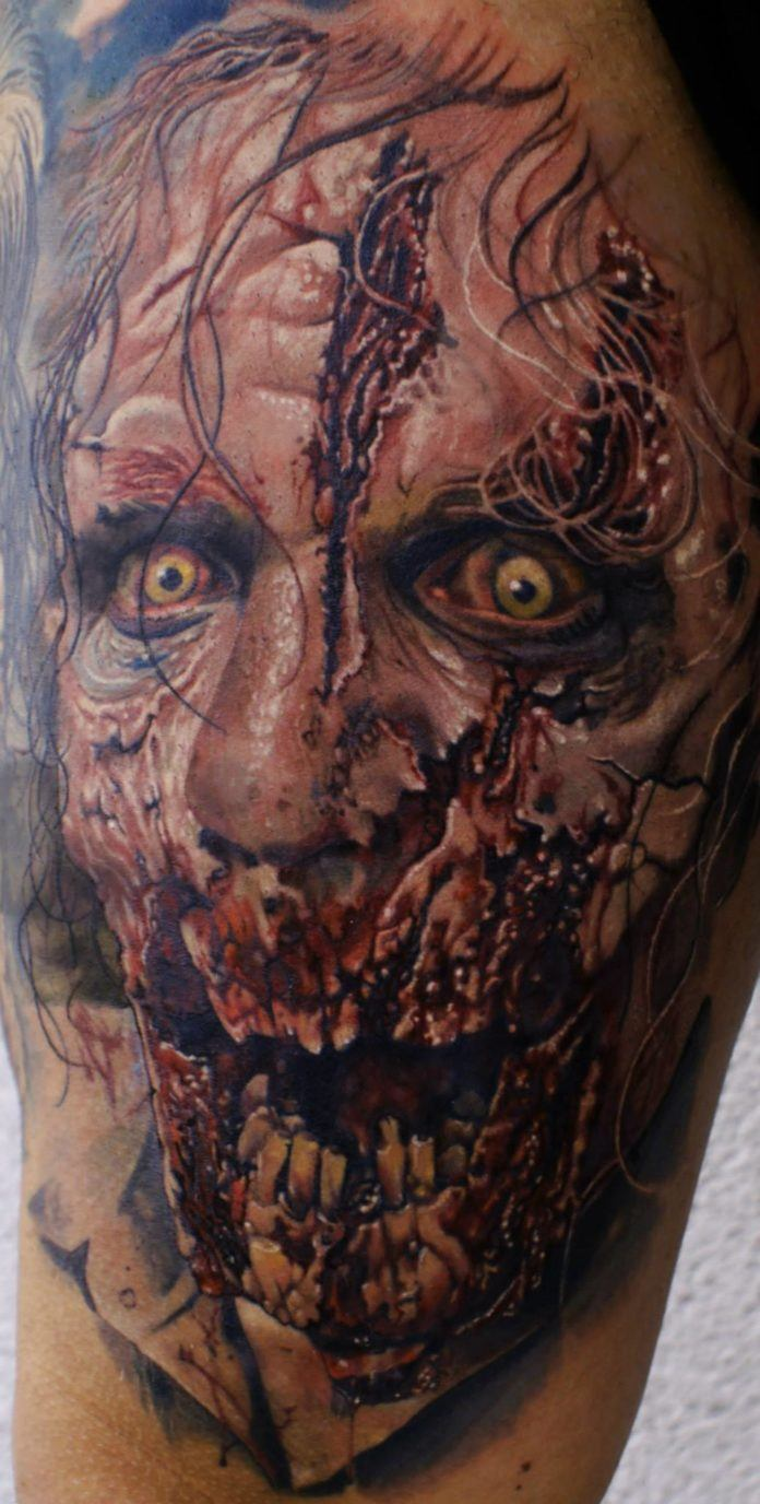 Creep yourself out with a horror tattoo like this rotting, hungry zombie tattoo by Mario Hartmann