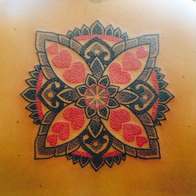 Italian tattoo artist Marco Galdo inserts red hearts into the petals of this mandala tattoo design