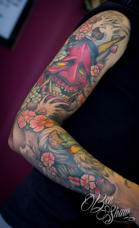 A Japanese demon grins out from behind the cover of cherry blossoms and waves in this life and death tattoo by Ben Shaw