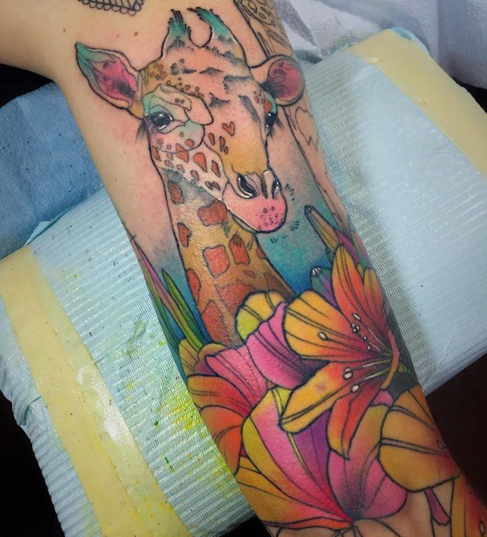 A baby giraffe peeks out over a bed of lily flowers in this colorful watercolor tattoo by Katie Shocrylas