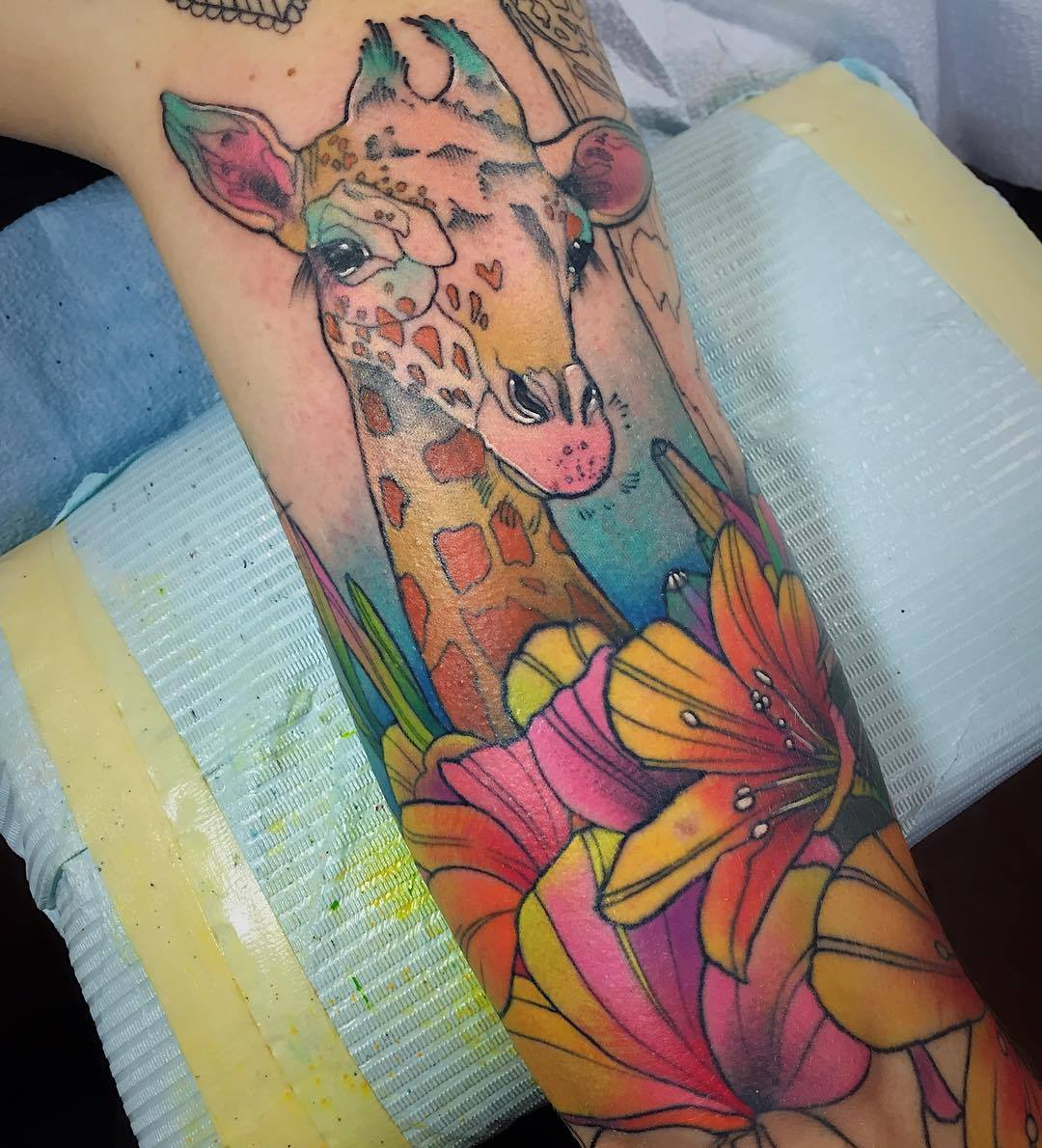 A baby giraffe peeks out over a bed of lily flowers in this colorful a baby giraffe peeks out over a bed of lily flowers in this colorful watercolor tattoo by katie shocrylas izmirmasajfo