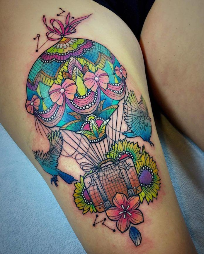A beautifully detailed hot air balloon carries an antique suitcase in this bright color watercolor tattoo by Katie Shocrylas