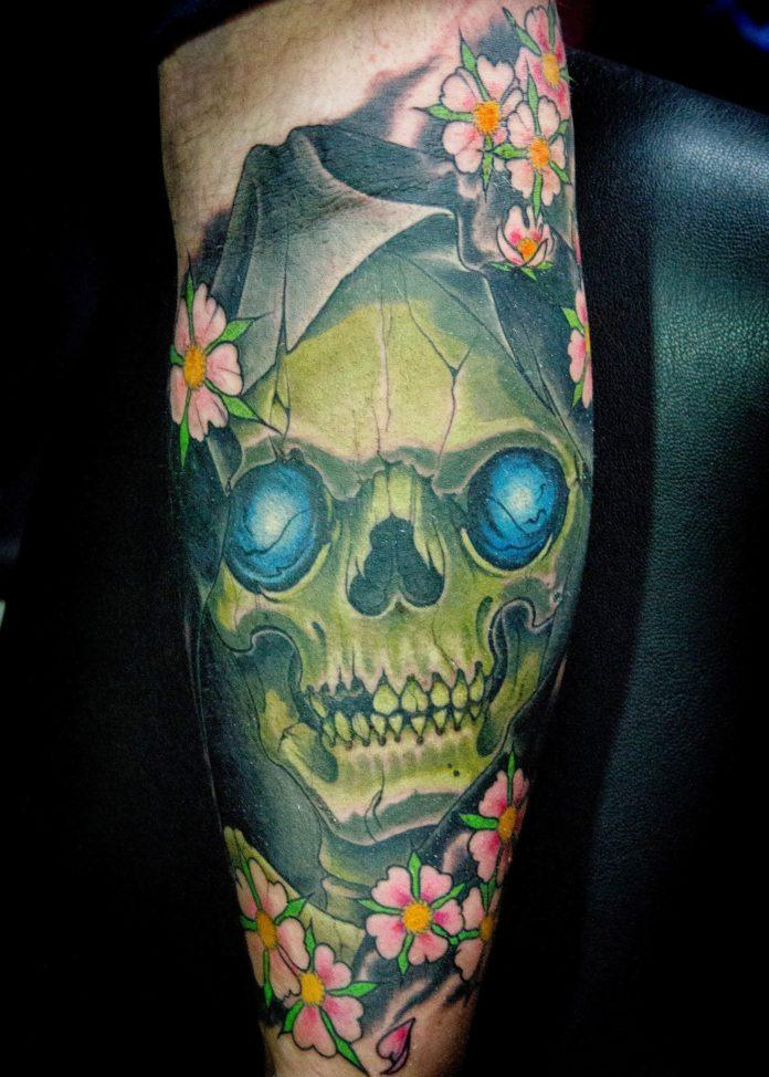 A hooded skull with glowing eyes watches the world from behind a cluster of cherry blossoms in this gothic tattoo by Ben Shaw.