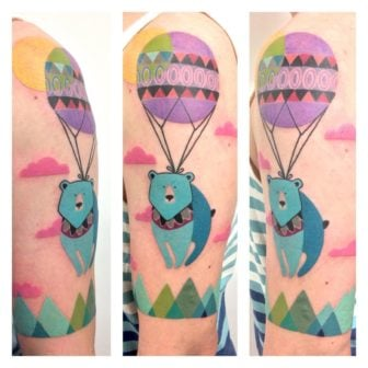 An adventurous bear takes to the skies in a colorful hot air balloon in this excellent tattoo by Amanda Chamfreau