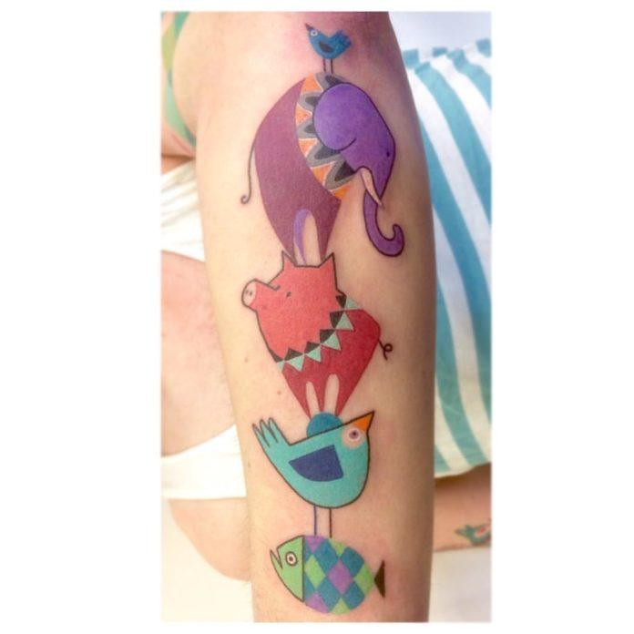 An elephant, a pig, a bird and a fish make an animal totem pole in this whimsical tattoo by Amanda Chamfreau