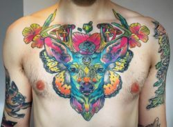 Katie Shocrylas' psychedelic tattoo of a deer features the animal posing with poppy flowers and magic mushrooms on a background of butterfly wings.