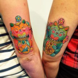 Maneki-neko (Chinese luck cats) feature in this watercolor friendship tattoo by Katie Shocrylas