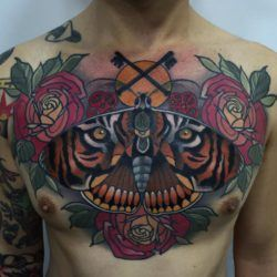 This incredible chest tattoo by Rodrigo Kalaka is a beautifully executed pun on the name of the tiger moth