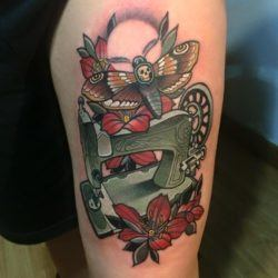 This neo traditional tattoo by Rodrigo Kalaka features a deaths head moth flying over an antique sewing machine.