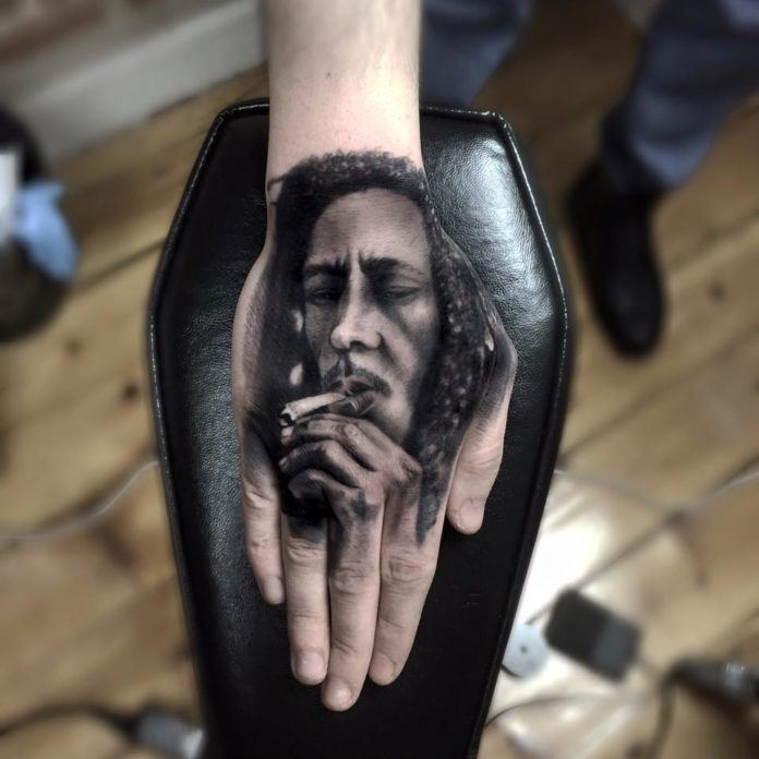 This photo realistic hand tattoo shows Bob Marley smoking a joint.