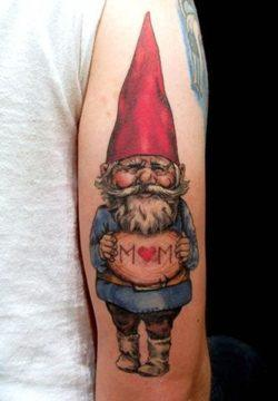A gnome holds up a sign that says MOM in this cute tattoo