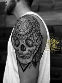 Life and death are balanced in this black ink tattoo by master tattooist Kirk Nilsen