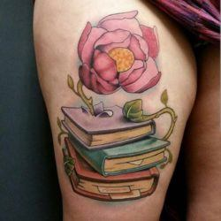 A flower grows out of a book in this book lovers tattoo