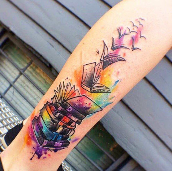 A pile of books takes flight as it transforms into a flock of birds in this colorful book tattoo for nature lovers