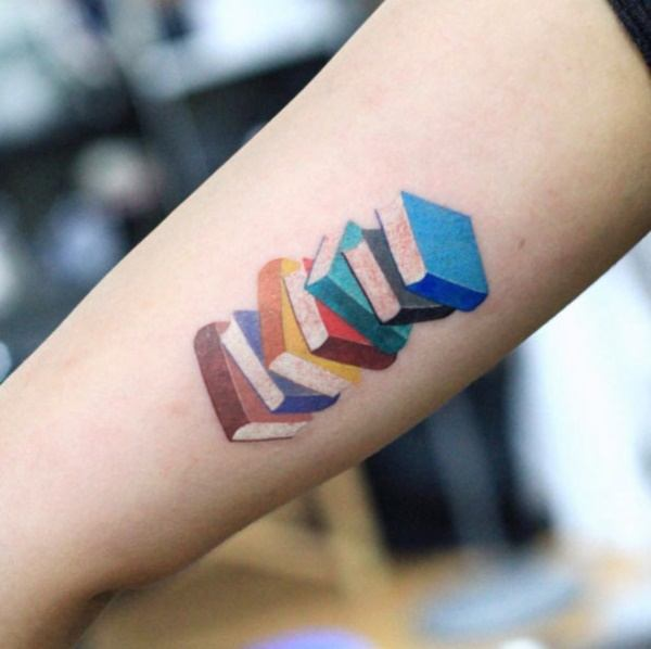 A pile of colorful books in a tattoo is a symbol that the tattoo wearer is a book lover