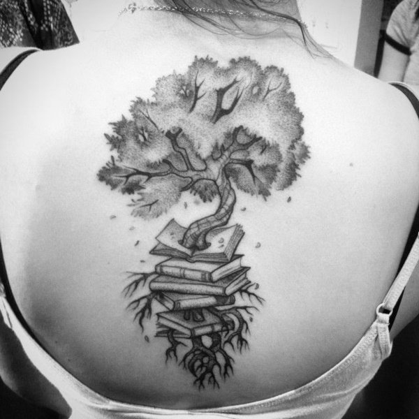 A tree grows out of a pile of books in this black ink tattoo