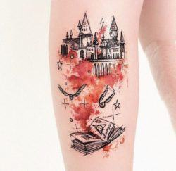 A vision of a fantasy town emerges from a book in this magical tattoo