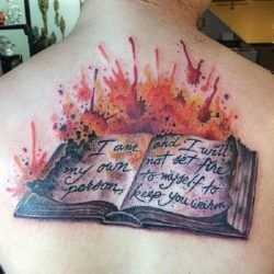 The words on the pages of this artistic book tattoo read, I am my own person and I will not set fire to myself to keep you warm.