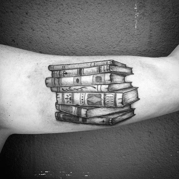 This beautiful black ink tattoo shows a professionally inked pile of books
