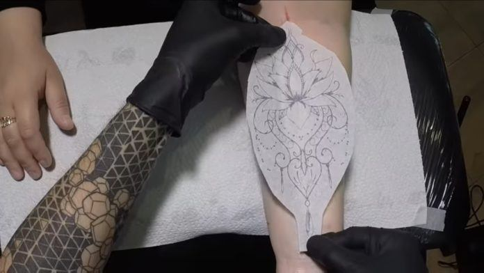 Tattooer Florin Zaharia transfers the hand drawn tattoo design on paper directly on to the skin of his tattoo client