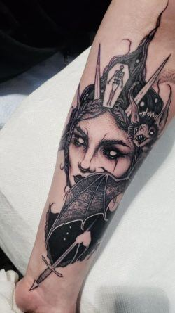 A bat, a coffin and a dagger act as jewelry and accessories for this dark witch tattoo by Ryan Murray