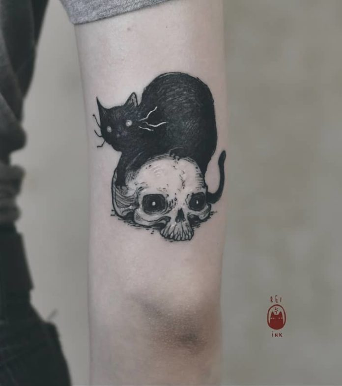 A black cat sits on top of a human skull in this elbow tattoo by Daria Rei