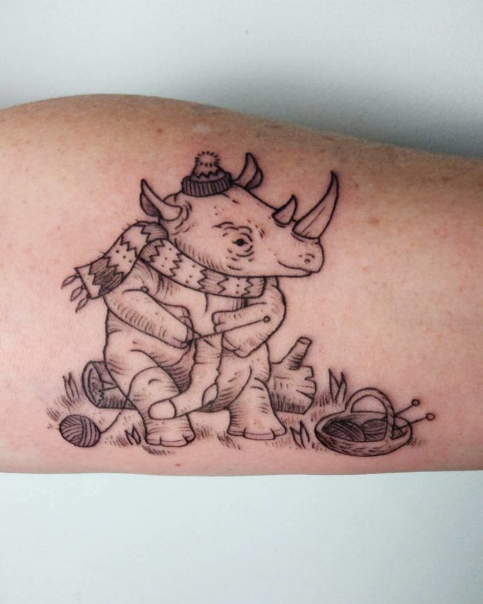 Alex Cfourpo has designed and tattooed this cartoon rhino sitting on a log and knitting a sock