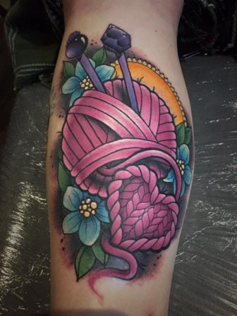Tattoo artist Leah Moule has added hearts and flowers into this colorful knitting tattoo to add to the feminine appeal of the tattoo design