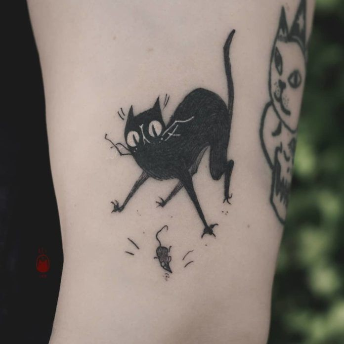 Tattooer Daria Rei's sense of humor can be seen in this funny tattoo of a black cat that's freaking out over the mouse it's just killed.