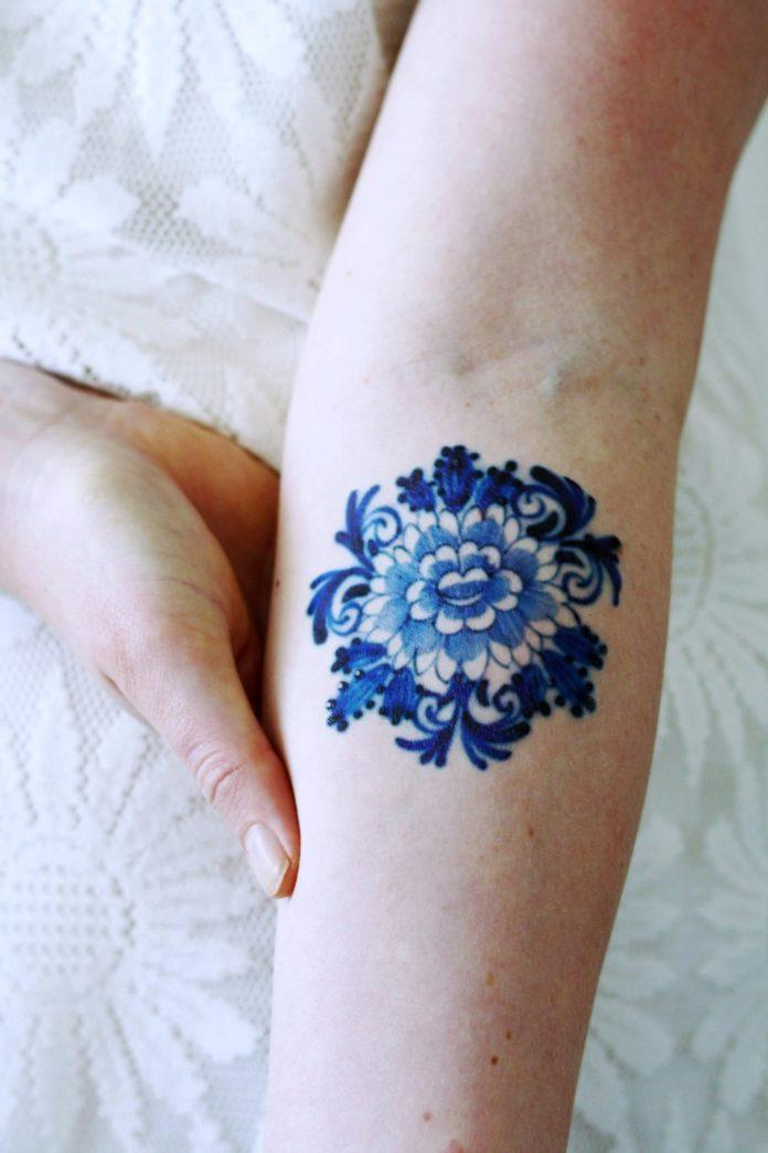 The designer has chosen to create this temporary tattoo of a flower in an art style known as Delft Blue