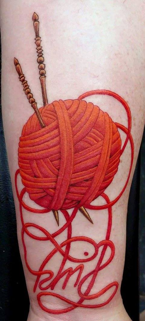 This beautiful tattoo, worn by knitwear designer Claudia Donnelly boats a beautiful red ball of yarn with gold knitting needles