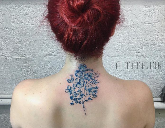 A small spray of wildflowers and foliage are the subject of this feminine neck tattoo by Patrícia Mara