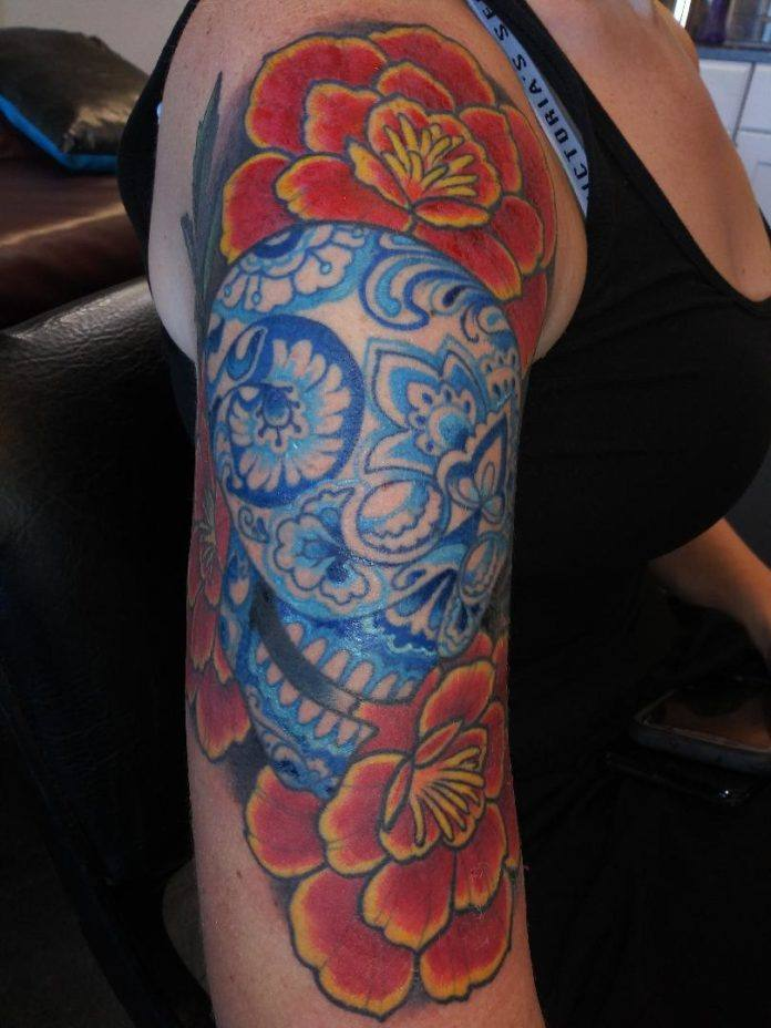 Eric at Cherry Street tattoo studio has created contrast between the floral Delft Blue skull and the bright red and yellow flowers behind it