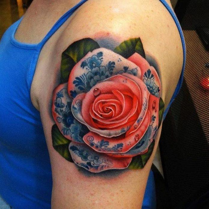 This stunning tattoo of a pink rose with Delft Blue floral ornaments is by Andres Acosta