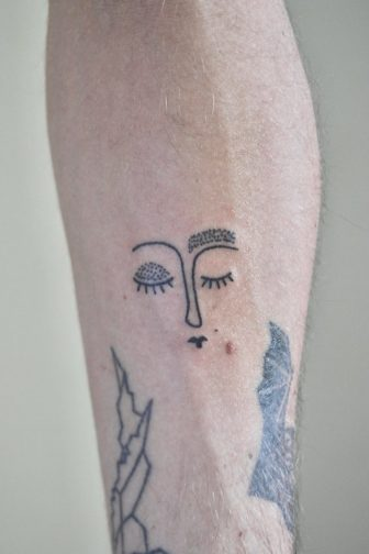 This abstract portrait tattoo uses dotwork to shade the eyelid and eyebrow of the sleeping woman